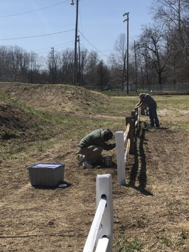 Volunteers painting section of fence