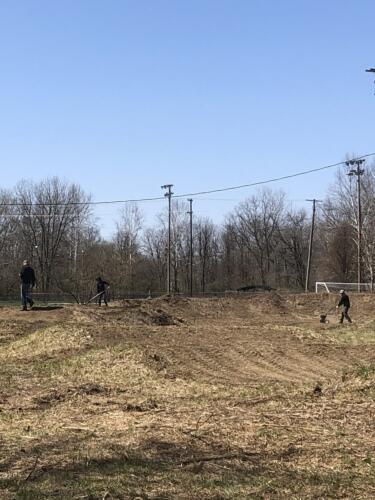 Volunteers smoothing last row of BMX track